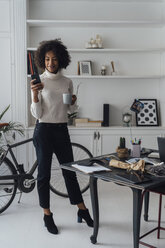 Mid adult freelancer standing in her home office, using smartphone, holding coffee cup - BOYF00921