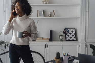 Mid adult freelancer standing in her home office, drinking coffee, talking on the phone - BOYF00924