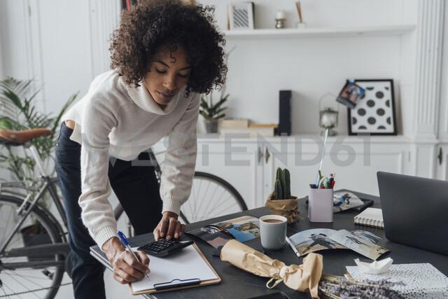 Freelancer standing at hert desk, using calculater, taking notes - BOYF00930 - Boy/Westend61