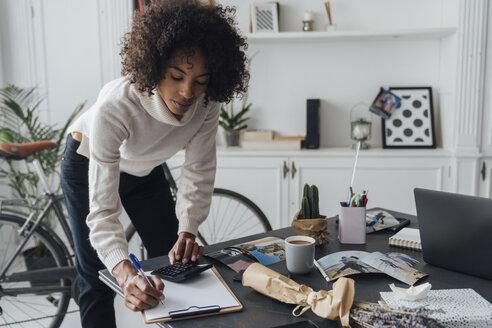 Freelancer standing at hert desk, using calculater, taking notes - BOYF00930