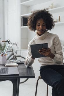 Mid adult freelancer sitting at her desk, working with laptop and digital tablet - BOYF00933