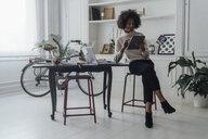 Mid adult freelancer sitting at her desk, working with laptop and digital tablet - BOYF00936