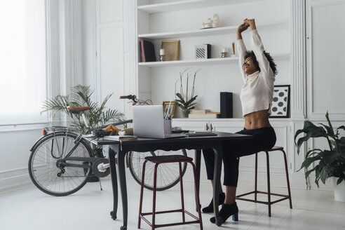 Mid adult woman sitting in her home office, smiling and stretching - BOYF00939