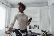 Mid adult woman leaving her home office, pushing bicycle, using smartphone - BOYF00945