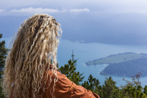Young woman hiking in the Bavarian mountains, looking at Lake Walchensee - TCF05907