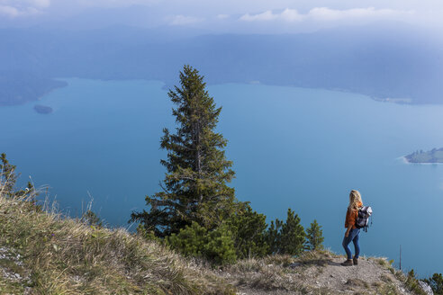 Young woman hiking in the Bavarian mountains, looking at Lake Walchensee - TCF05913