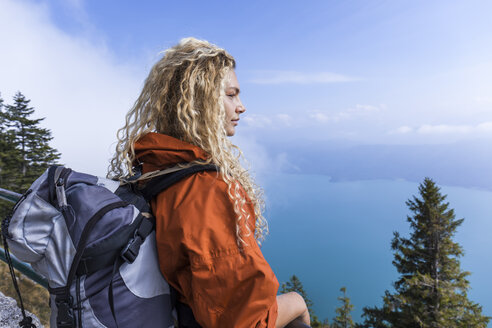 Young woman hiking in the Bavarian mountains, looking at Lake Walchensee - TCF05916