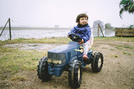 Baby girl driving a toy tractor next to the rice fields - GEMF02501