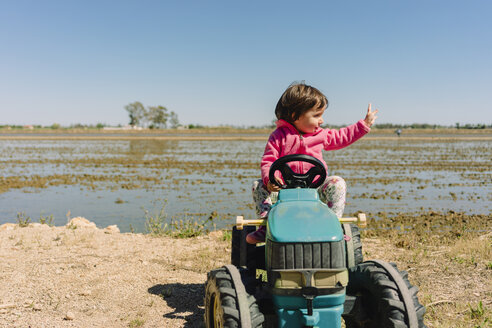 Baby girl driving a toy tractor next to the rice fields - GEMF02513