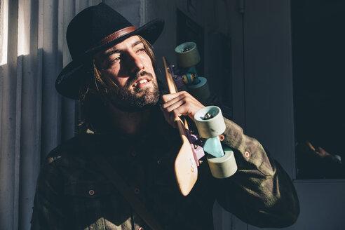USA, New York City, portrait of bearded man with skateboard wearing black hat - OCMF00098