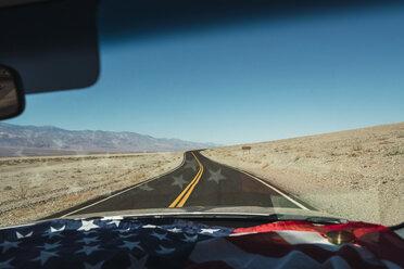 USA, California, Death Valley, American flag lying on dashboard of car - KKAF02956