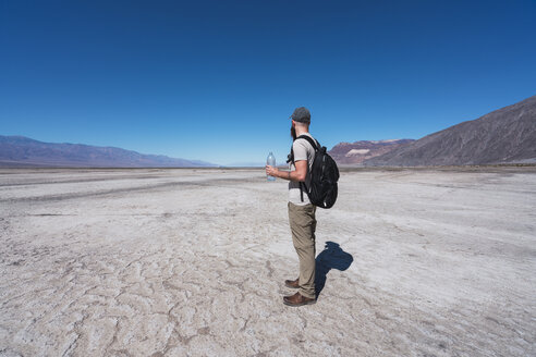 USA, California, Death Valley, man with backpack and water bottle standing in desert looking at distance - KKAF02959