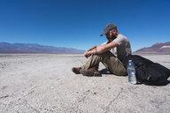 USA, California, Death Valley, man sitting on ground in the desert having a rest - KKAF02962