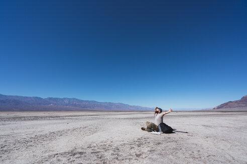 USA, California, Death Valley, man sitting on ground in the desert - KKAF02965