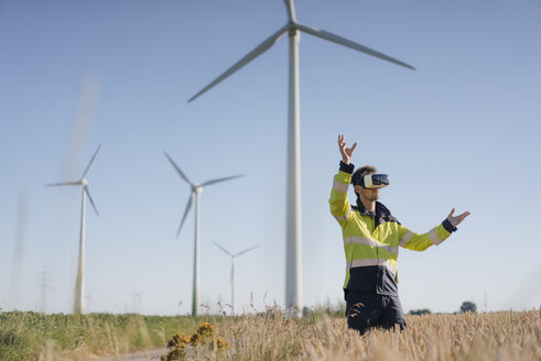 Engineer standing in a field at a wind farm wearing VR glasses - GUSF01308