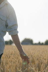 Close-up of man in a field touching ears - GUSF01314