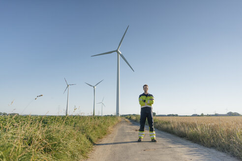 Engineer standing on field path at a wind farm - GUSF01317