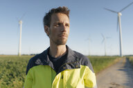 Portrait of an engineer on field path at a wind farm - GUSF01320