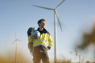 Technician standing in a field at a wind farm with climbing equipment - GUSF01329