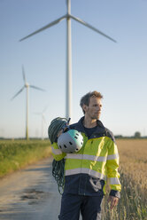 Technician standing on field path at a wind farm with climbing equipment - GUSF01332