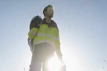 Technician with climbing equipment under blue sky - GUSF01335
