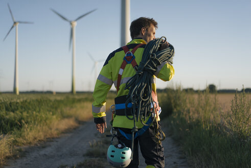 Technician walking on field path at a wind farm with climbing equipment - GUSF01338