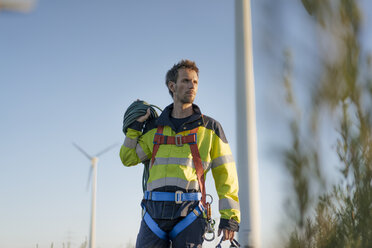 Technician standing at a wind farm with climbing equipment - GUSF01341
