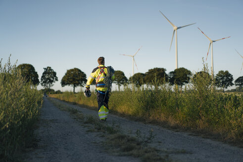 Technician walking on field path at a wind farm with climbing equipment - GUSF01344