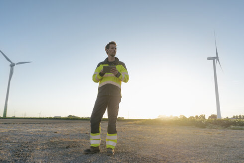 Engineer standing in rural landscape at a wind farm holding tablet - GUSF01347