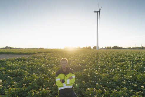 Engineer standing in a field at a wind turbine - GUSF01350