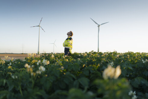 Engineer standing in a field at a wind farm - GUSF01353