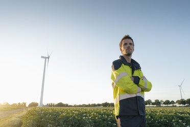 Engineer standing in a field at a wind turbine - GUSF01356