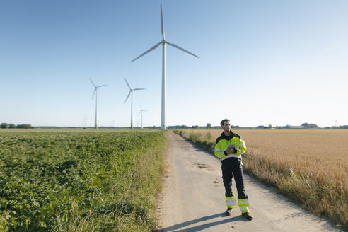 Engineer standing on field path at a wind farm - GUSF01362