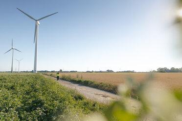 Engineer walking on field path at a wind farm - GUSF01365