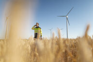 Engineer standing in a field at a wind farm talking on cell phone - GUSF01368
