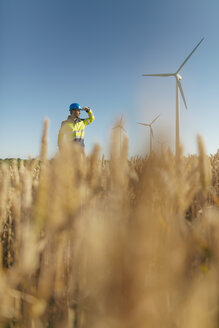 Engineer standing in a field at a wind farm - GUSF01371