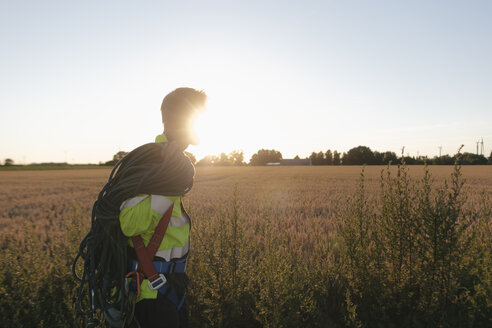 Technician with climbing equipment at a field in sunset - GUSF01374