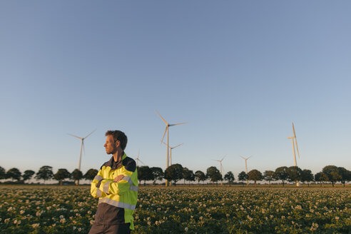 Engineer standing in a field at a wind farm - GUSF01377