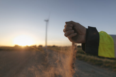 Close-up of man's hand scattering soil at a wind turbine at sunset - GUSF01380