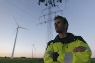 Portrait of an engineer next to a wind farm and power pole - GUSF01386