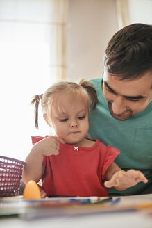 Portrait of little girl drawing with coloured pencils while her father watching her - ZEDF01758