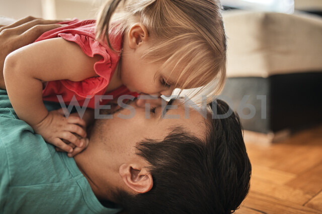 Father and little daughter cuddling together at home - ZEDF01764
