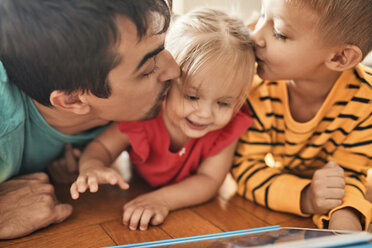 Father and brother kissing happy little girl - ZEDF01770
