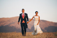 Happy bride and groom walking in mountains - OCMF00103
