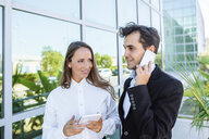 Smiling businesswoman and businessman with tablet and cell phone outside office building - KIJF02096