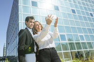 Smiling businesswoman and businessman taking a selfie outside office building - KIJF02099