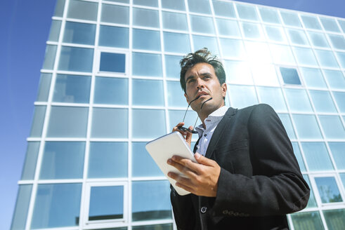 Businessman with tablet and sunglasses outside office building - KIJF02102