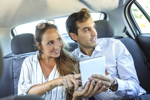 Couple using tablet on back seat of a car - KIJF02105