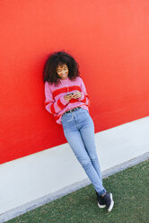 Smiling young woman with earphones leaning against red wall looking at cell phone - KIJF02123