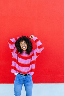 Portrait of laughing young woman with curly hair standing in front of red wall - KIJF02126